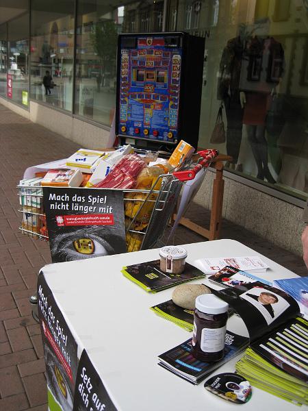 Einkaufswagen mit dem Wert eines Stundenverlustes am Geldspielautomaten und der Infotisch der Suchtberatungsstelle der Caritas Neunkirchen