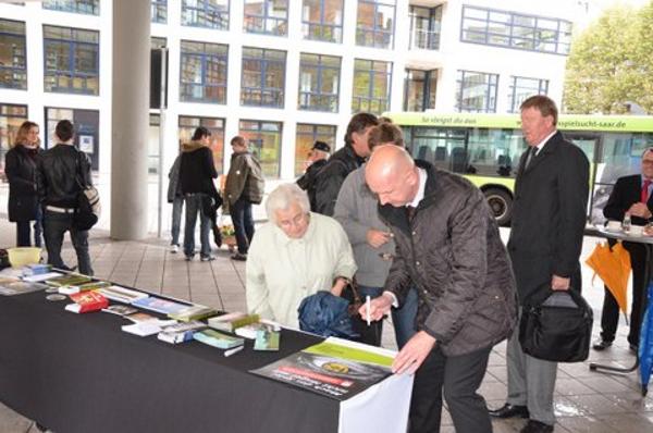 Saarbahn-Geschäftsführer Norbert Reuter beim signieren unseres Werbeplakates