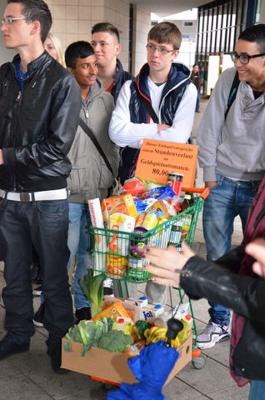 Schüler mit dem Lebensmittelkorb im Wert eines Stundenverlustes (80,00 EUR) an einem Geldspielautomaten.